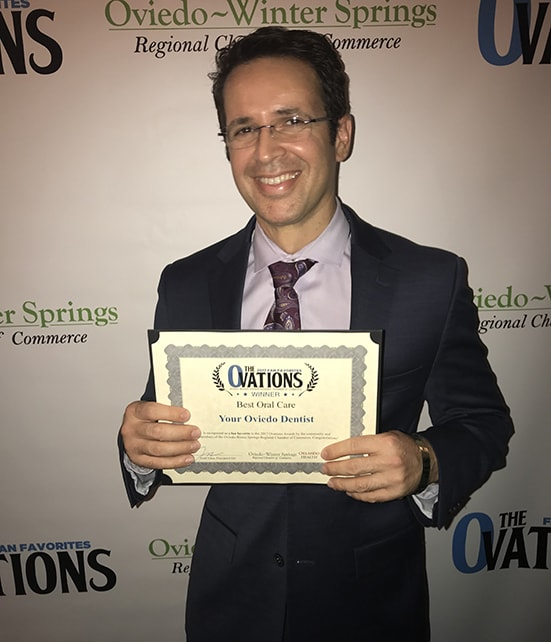 "Dr. Angel Lopez holding ""Best Oral Care"" award from Oviedo Winter Springs"