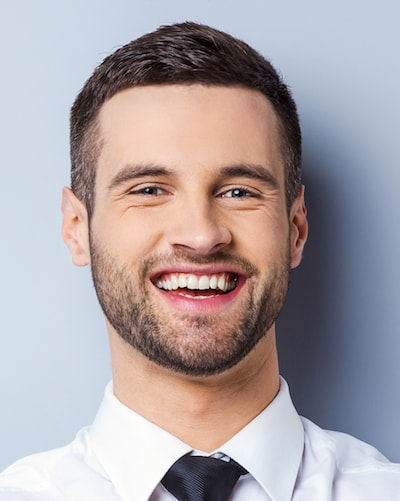 Cosmetic Dentistry Oviedo - Young man showing his new whitened teeth