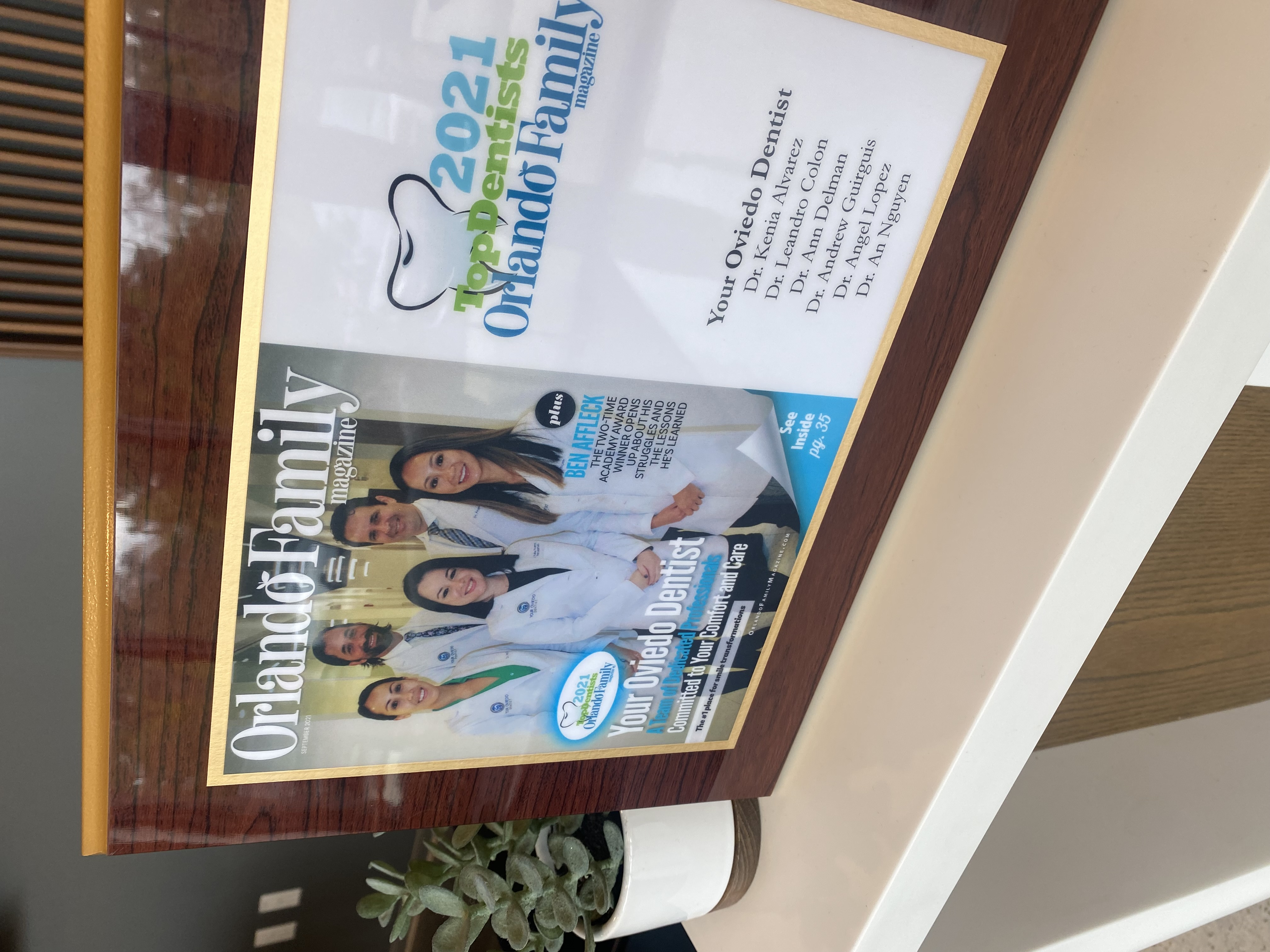 """Dr. Angel Lopez holding """"Best Oral Care"""" award from Oviedo Winter Springs"""